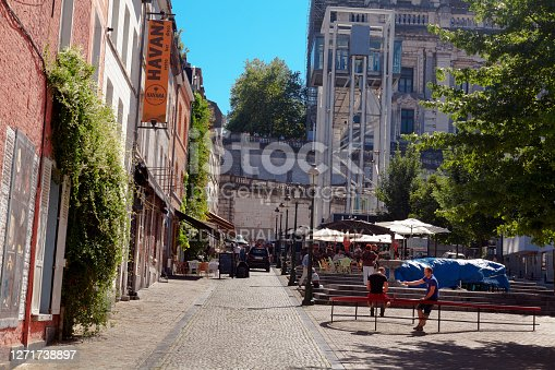 View into street Rue de l'Epée  in Brussels in district Marolles below elevator of Marolles in background. In street are bars. A few people are in square like area. In background are parasols and seats