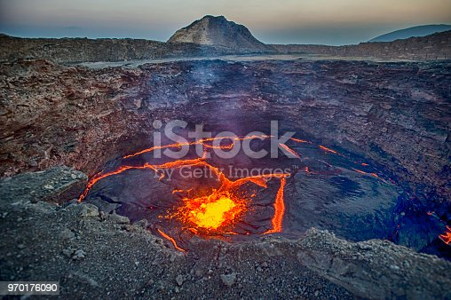View from the crater rim of Erta Ale - one of the most active vulancoes in the world - into the active, red glowing lava lake. Erta Ale is a continuously active basaltic shield volcano in the Afar Region of northeastern Ethiopia, only some kilometers from the border to Eritrea.  The Afar Depression (or Danakil Depression) in the border-triangle between Ethiopia, Eritrea and Djibouti is one of the most remote and most extreme regions of the world - it is the lowest point in Africa (- 155 metres/-550 ft below sea level) and one of the hottest places on Earth.  The Danakil/Afar Depression is the product of a tectonic triple junction, where the spreading ridges that form the Red Sea and the Gulf of Aden emerge on land and meet the East African Rift. Here the Earth's crust is slowly rifting apart at a rate of 1–2 centimetres (0.3–0.8 in) per year.  Erta ale is ond of the most dangerous places on earth - the lat major eruptions took place in September 2005, August 2007 and November 2008.