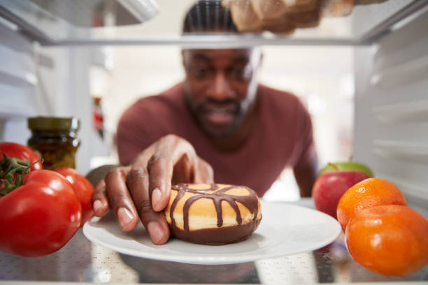 View Looking Out From Inside Of Refrigerator As Man Opens Door And Reaches For Unhealthy Donut View Looking Out From Inside Of Refrigerator As Man Opens Door And Reaches For Unhealthy Donut temptation stock pictures, royalty-free photos & images