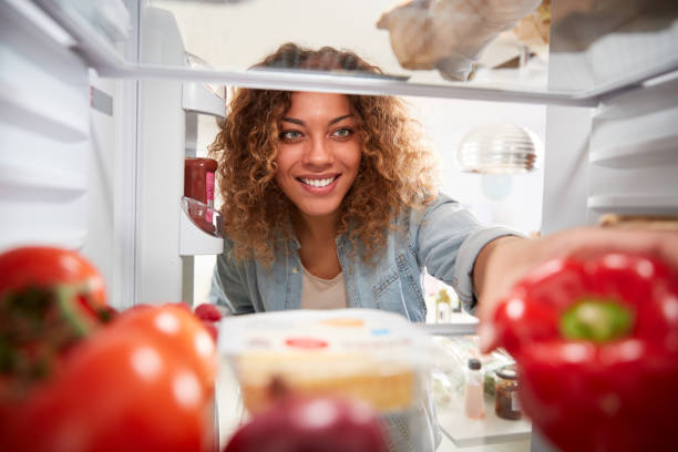 View Looking Out From Inside Of Refrigerator As Woman Opens Door And Unpacks Shopping Bag Of Food View Looking Out From Inside Of Refrigerator As Woman Opens Door And Unpacks Shopping Bag Of Food fridge stock pictures, royalty-free photos & images