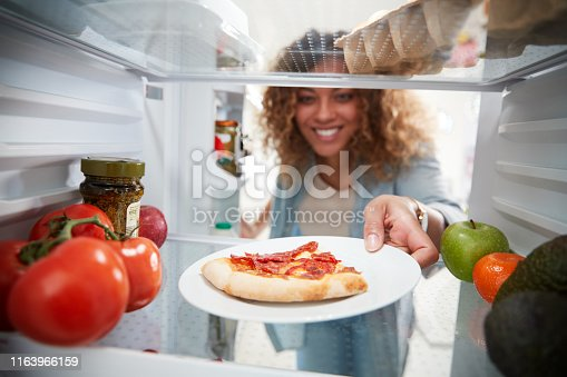View Looking Out From Inside Of Refrigerator As Woman Opens Door For Leftover Takeaway Pizza Slice