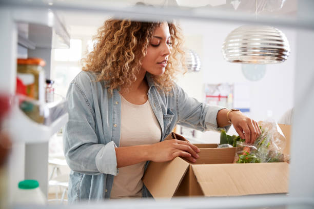 view looking out from inside of refrigerator as woman unpacks online home food delivery - delivery стоковые фото и изображения