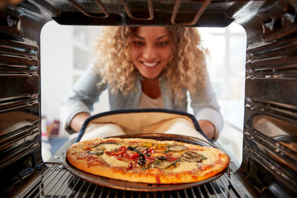 View Looking Out From Inside Oven As Woman Cooks Fresh Pizza View Looking Out From Inside Oven As Woman Cooks Fresh Pizza oven stock pictures, royalty-free photos & images