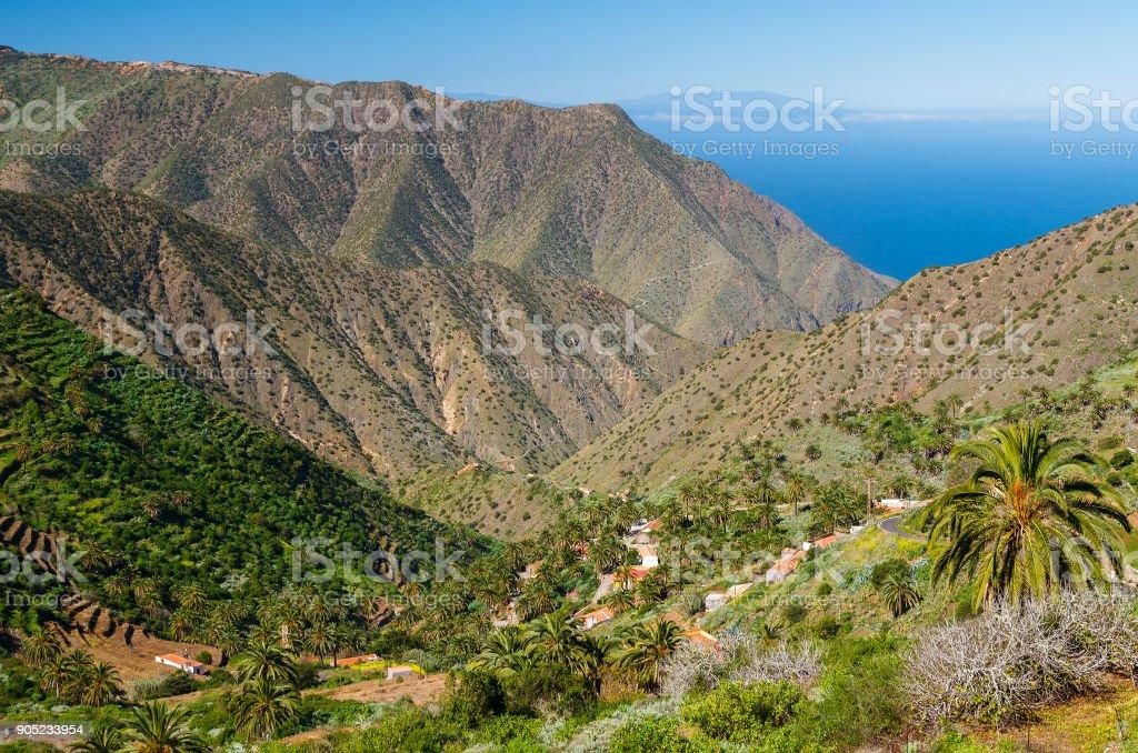 View mountain valley palm tree blue ocean sea, Agulo, La Gomera, Canary Islands stock photo