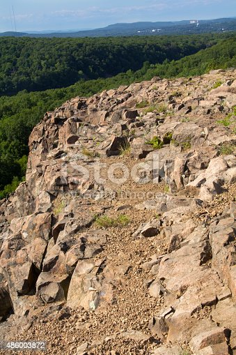 West ridge and cliffs of Ragged Mountain, along the Metacomet Trail in Berlin, Connecticut. Volcanic rocks typical of the Metacomet Ridge are in the foreground. Vertical image.