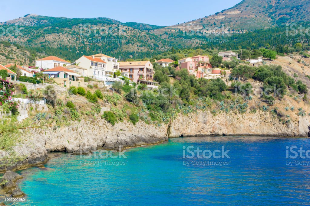 View of a bay with turquoise waters and traditional colorful houses in Assos village, Kefalonia, Greec stock photo