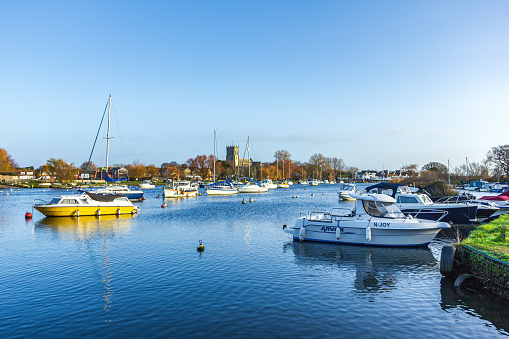 A view of a beautiful calm river marina with boats along grassy banks and church in the background under a majestic blue sky