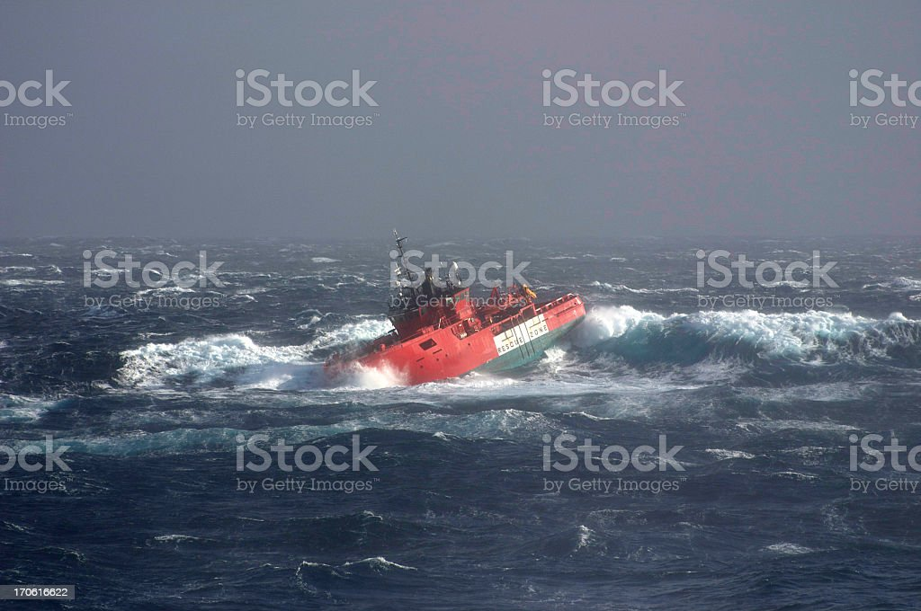 View of a boat drifting in a stormy sea stock photo