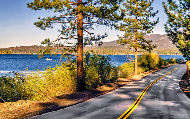 View of a California highway alongside Big Bear Lake. View of California road alongside Big Bear Lake, a preferred weekend and vacation destination all year round. san bernardino california stock pictures, royalty-free photos & images