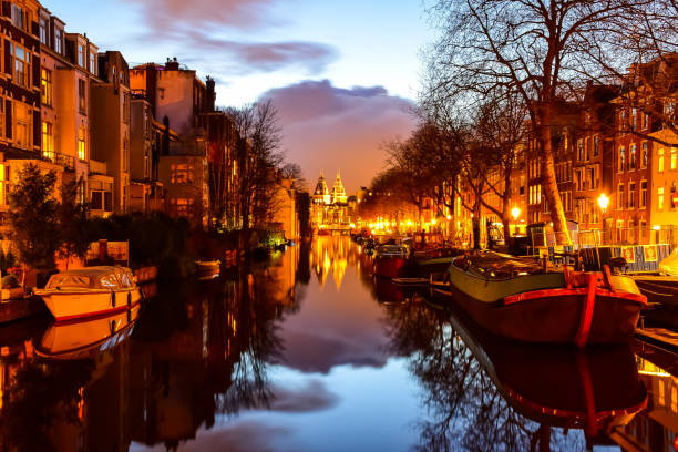 View of a canal at night with the Rijksmuseum in the background in Amsterdam, Netherlands twilight magic rijksmuseum stock pictures, royalty-free photos & images