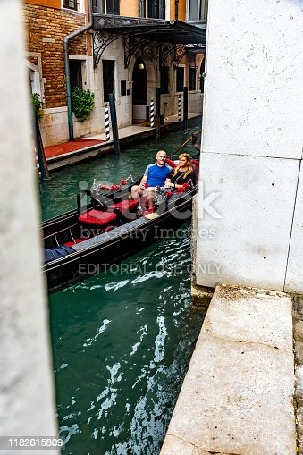 View through a bridge of a canal in Venice with a close-up of a gondola with a mature couple of tourists on board.