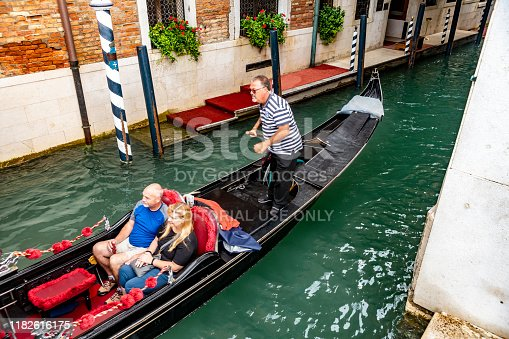 View through a bridge of a canal in Venice with a close-up of a gondolier with mature tourists in the gondola.