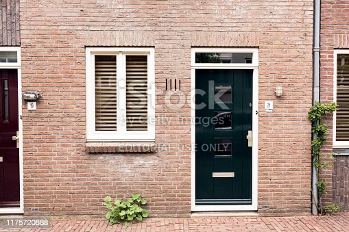 Deventer / The Netherlands - July 2019: View of a characteristic brick house front / facade with wooden doors with lintel panels, flower gardens in the center of Deventer, The Netherlands.