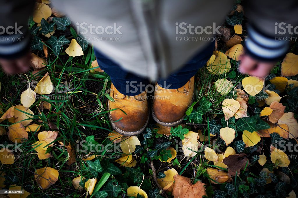 View of a child standing in fallen leaves stock photo