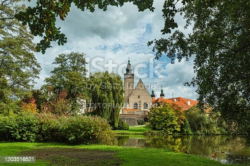 Telc / Czech Republic - September 27 2019: View from a castle garden over a lake with ducks framed with green trees. Autumn landscape scenery with blue sky and clouds.