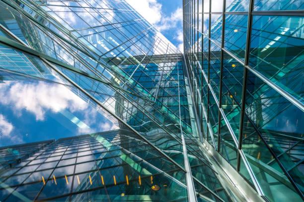 Blick auf ein zeitgenössisches Glashochhaus, das den blauen Himmel reflektiert- – Foto