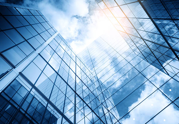 view of a contemporary glass skyscraper reflecting the blue sky view of a contemporary glass skyscraper reflecting the blue sky skyscraper stock pictures, royalty-free photos & images