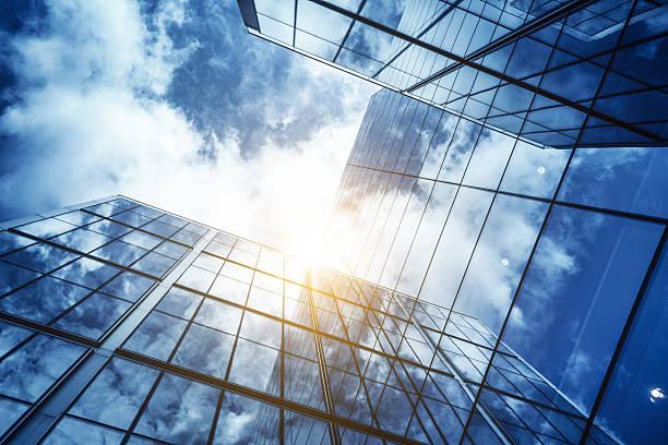 blick auf eine moderne glas wolkenkratzer, die den blauen himmel - fassadenschnitt stock-fotos und bilder