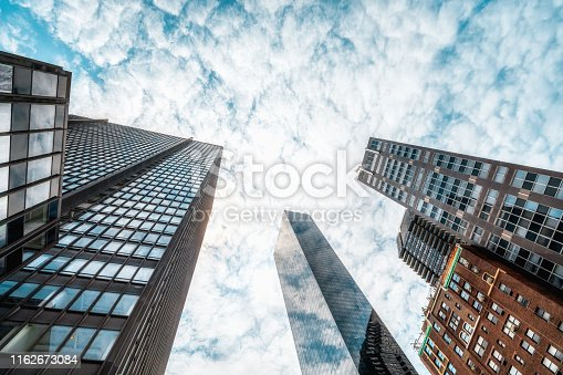 490774222istockphoto View of a Contemporary Glass Skyscrapers Reflecting Cloudy Sky 1162673084