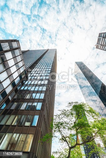 490774222istockphoto View of a Contemporary Glass Skyscrapers Reflecting Cloudy Sky, Vertical Banner 1162673609