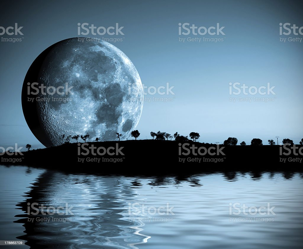 View of a full moon rising over the water and an island royalty-free stock photo