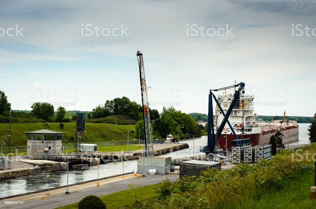 View of a Great Lakes Freight ship heading out of locks downward on the St. Lawrence River at Iroquois locks stock photo
