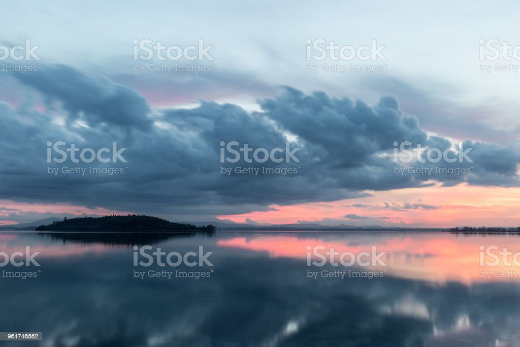 View of a lake at sunset, with perfect reflections of an island royalty-free stock photo