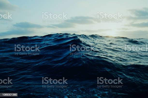 Photo of view of a large wave far out at the ocean from a sailboat