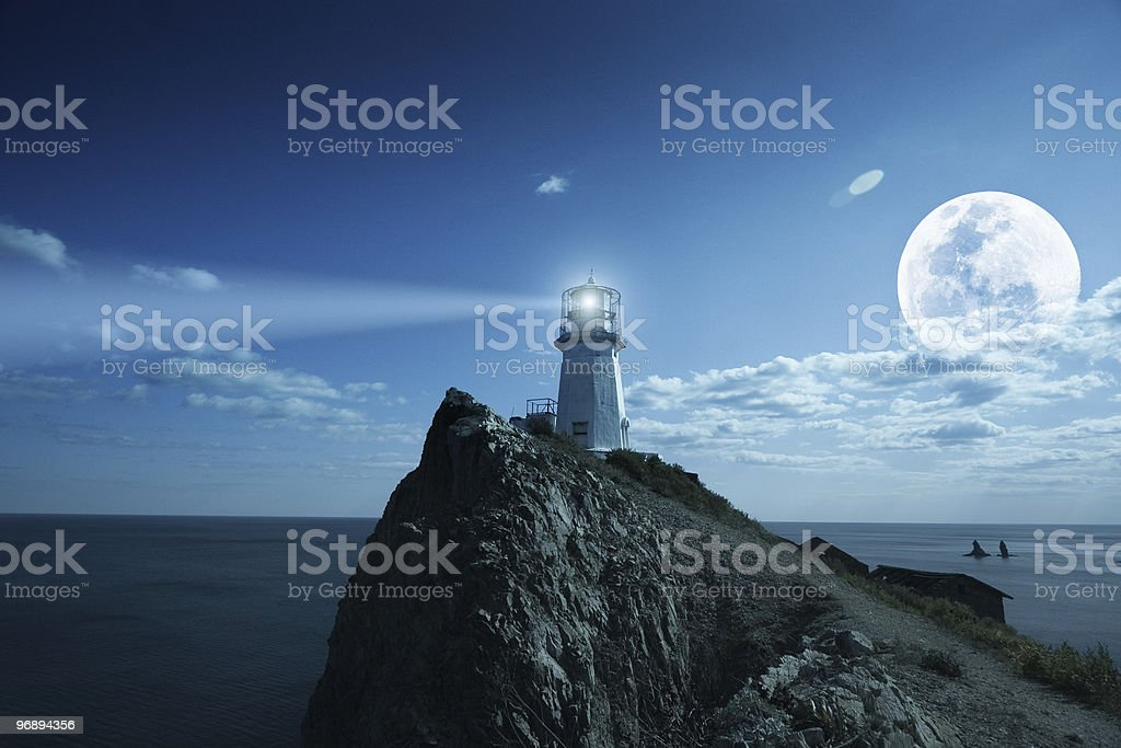 A view of a lighthouse on a cliff at night time royalty-free stock photo