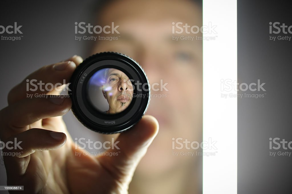 A view of a man looking through a camera lens stock photo