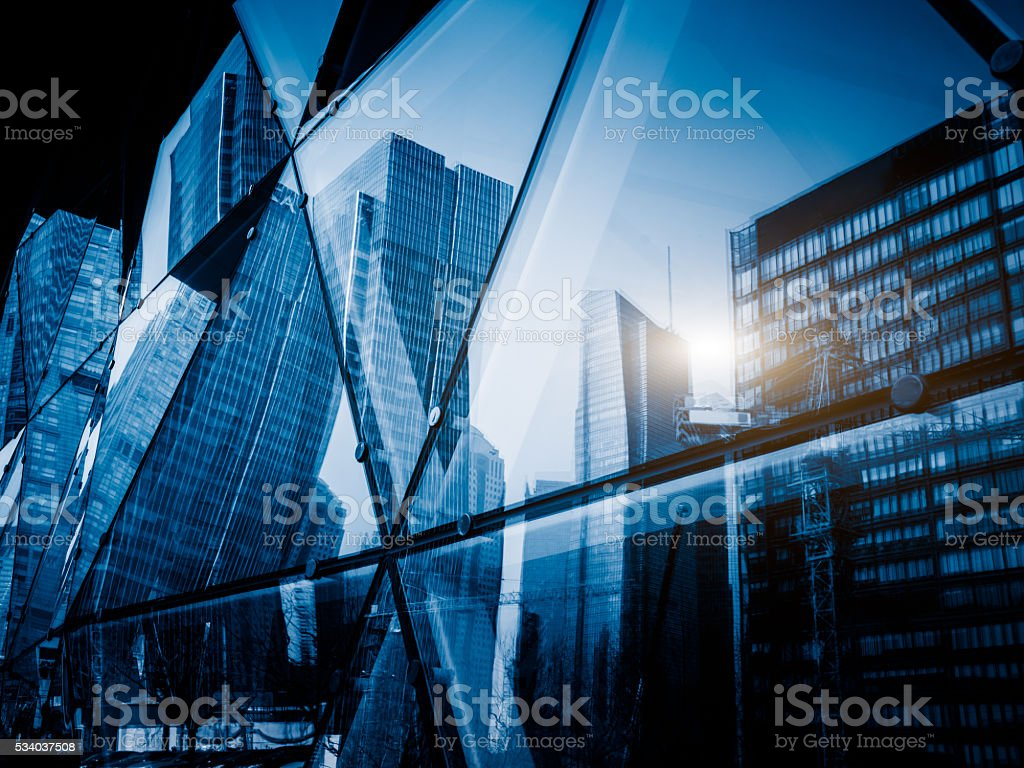 View of a modern glass skyscraper reflecting the buildings around stock photo