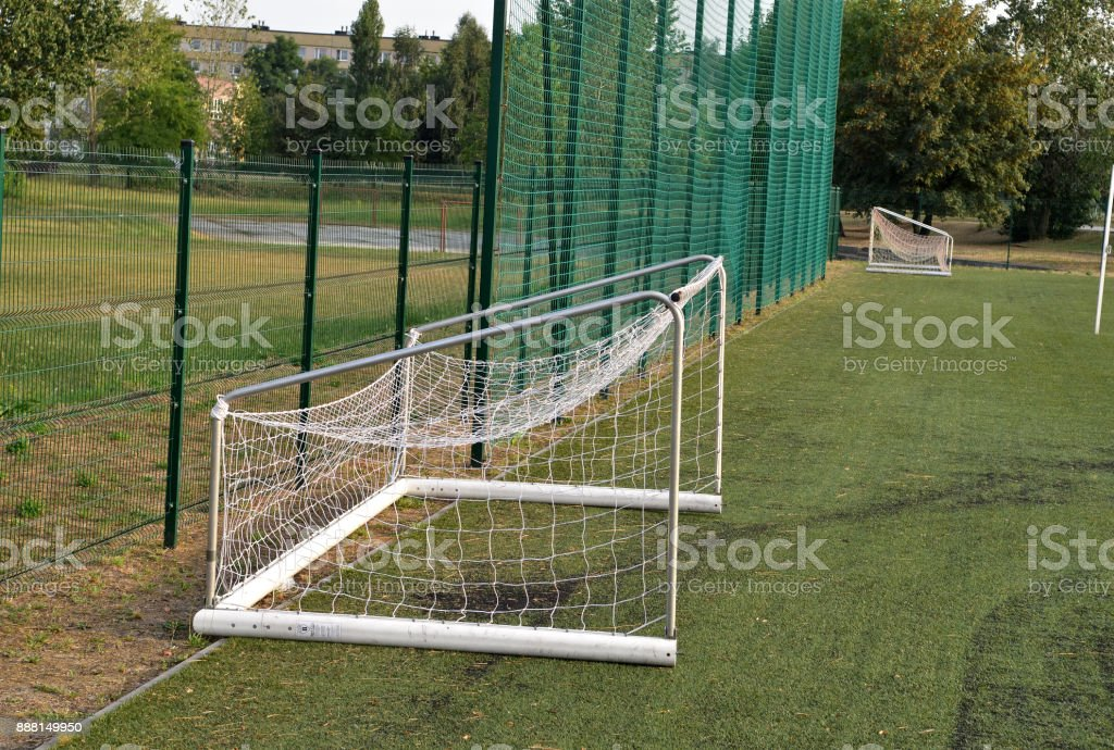 A view of a net on a vacant soccer pitch. stock photo