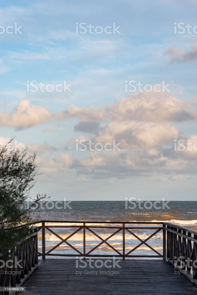 View of a path made of wood with a railing in the end, and the view...