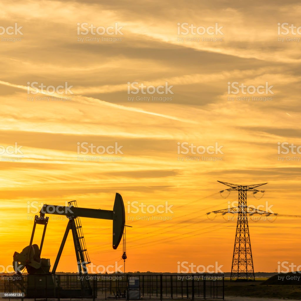 View Of A Pumpjack At Sunset Pumping Oil Out Of A Well In The Center
