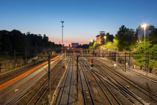 A view of a railroad junction with light trail of a passing by train. stock photo
