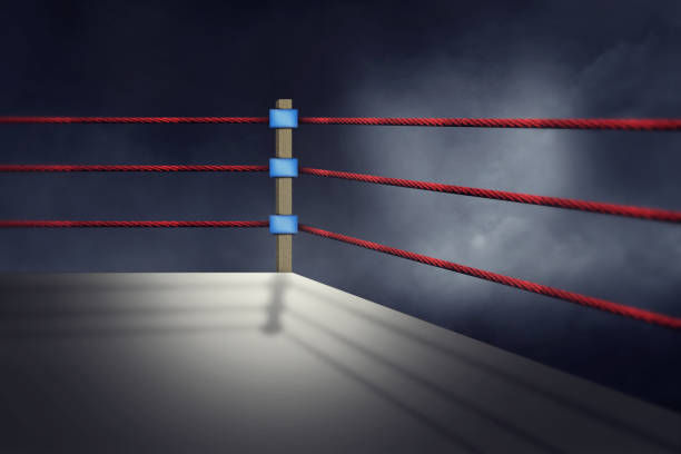 view of a regular boxing ring surrounded by red ropes spotlit by a spotlight - wrestling stock photos and pictures
