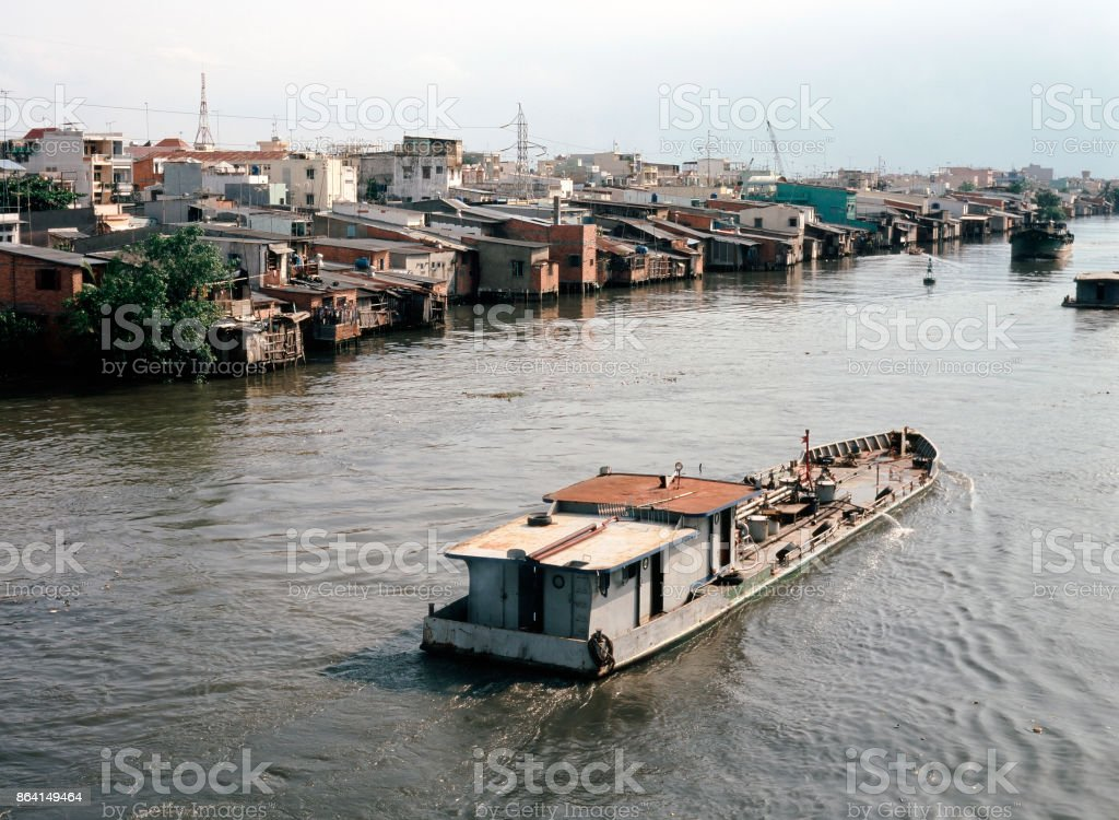 A view of a river, boats and fisherman and the city of Saigon, Vietnam royalty-free stock photo