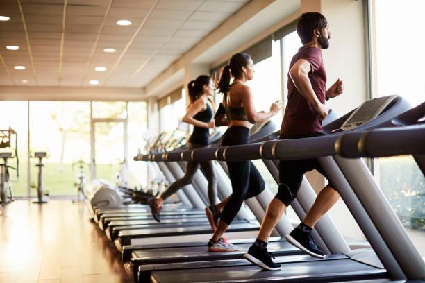 Blick auf eine Reihe von Laufbändern in einem Fitnessstudio mit Menschen. – Foto