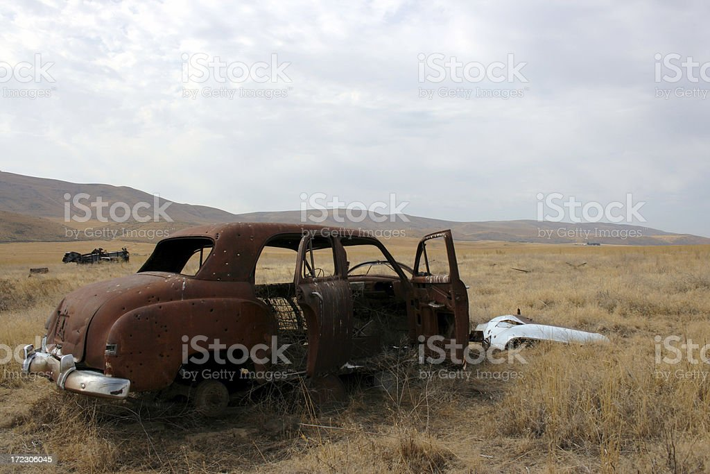 View of a rusty abandoned car in brown fields stock photo