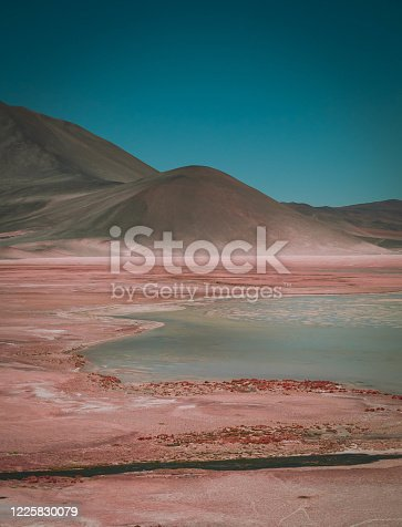 Atacama Desert in Chile. View of a beautiful lagoon and salt flat desert around it with the volcano on a background.