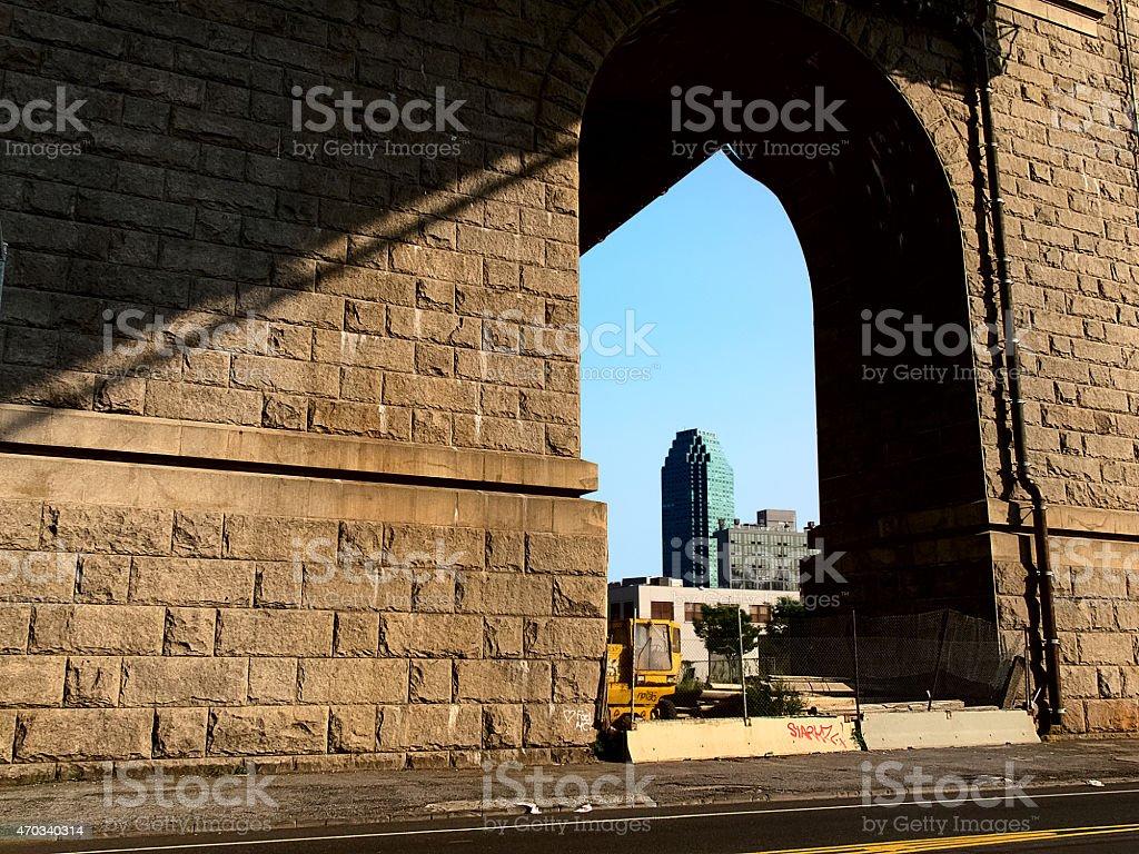 view of a skyscraper under the bridge stock photo