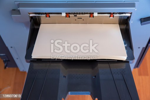 Close-up view of a stack of paper lying on a paper printing machine
