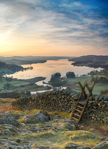 View of a sunrise over Windermere in the Lake District A picturesque view from Loughrigg Terrace looking across Windermere lake in the Lake District as the sun rises and casts early light on a stone wall and stile english lake district stock pictures, royalty-free photos & images