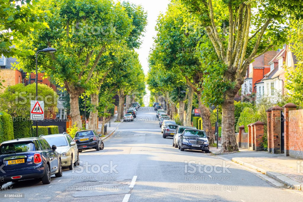 View of a treelined uphill street with a school children sign in West Hampstead, London stock photo