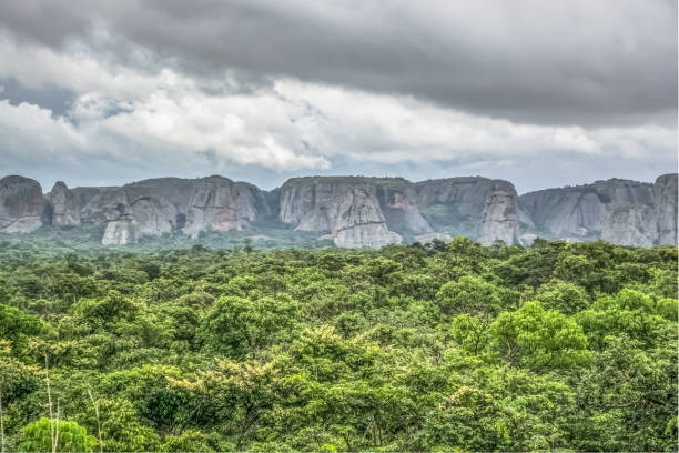 view of a tropical landscape, with forest and mountains pungo andongo, pedras negras , black stones, huge geologic rock elements, cloudy sky as background - angola stock photos and pictures
