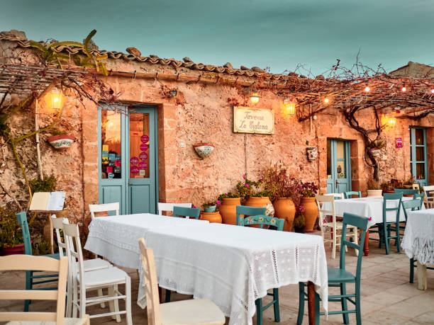 View of a typical restaurant in Marzamemi at sunset. Marzamemi, Sicily Marzamemi, Sicily - January 01, 2018: View of a typical restaurant in Marzamemi at sunset. Marzamemi, Sicily sicily stock pictures, royalty-free photos & images