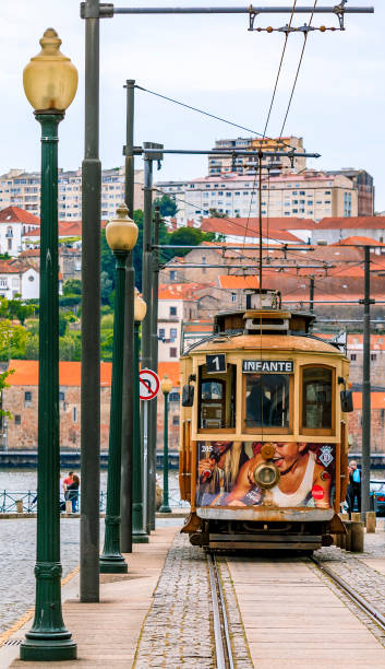 View of a typical street in the old town Ribeira neighborhood with a classic retro tourist tram car in Porto, Portugal stock photo