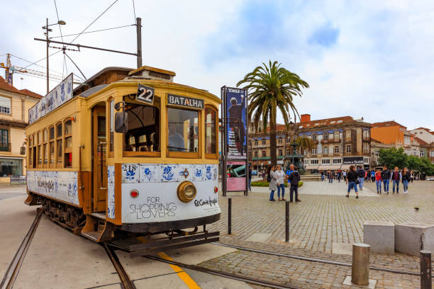 View of a typical street in the old town with a classic retro tourist tram car and people walking around Porto, Portugal stock photo