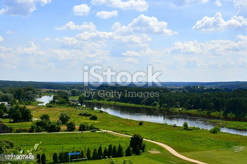 A view of a vast body of water flowing next to a lawn, meadow, or pastureland with a dirt road leading through it and some trees growing nearby seen on a cloudy summer day in Poland