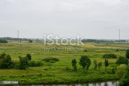A view of a vast field, meadow or pastureland with some trees and bushes growing near it located next to a shallow yet long river or lake see from the top of a tall hill on a Polish countryside